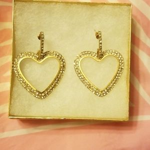 A pair of large heart hoop style earrings.